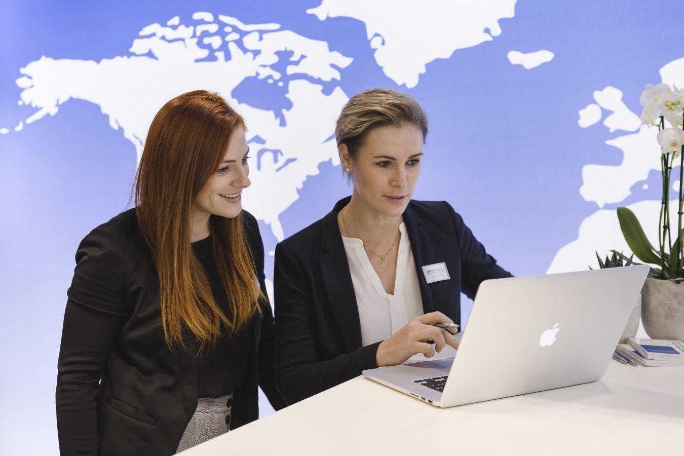 Businessreportage - Die Mitarbeiter stehen am Messestand und schauen etwas auf dem Rechner an