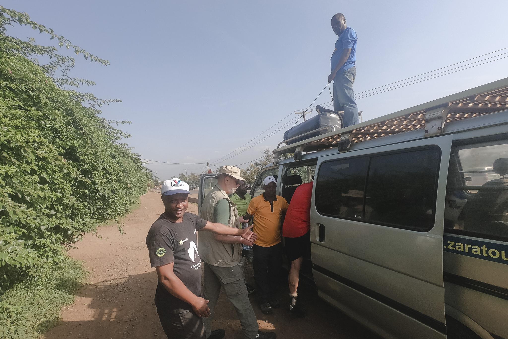 die Träger verstauen das Gepäck auf dem Autodach