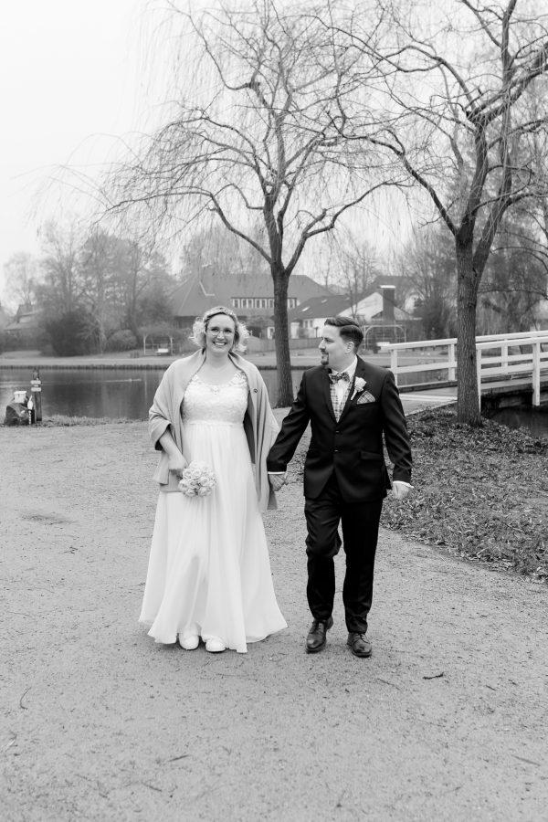 Brautpaar geht Hand in Hand am See entlang