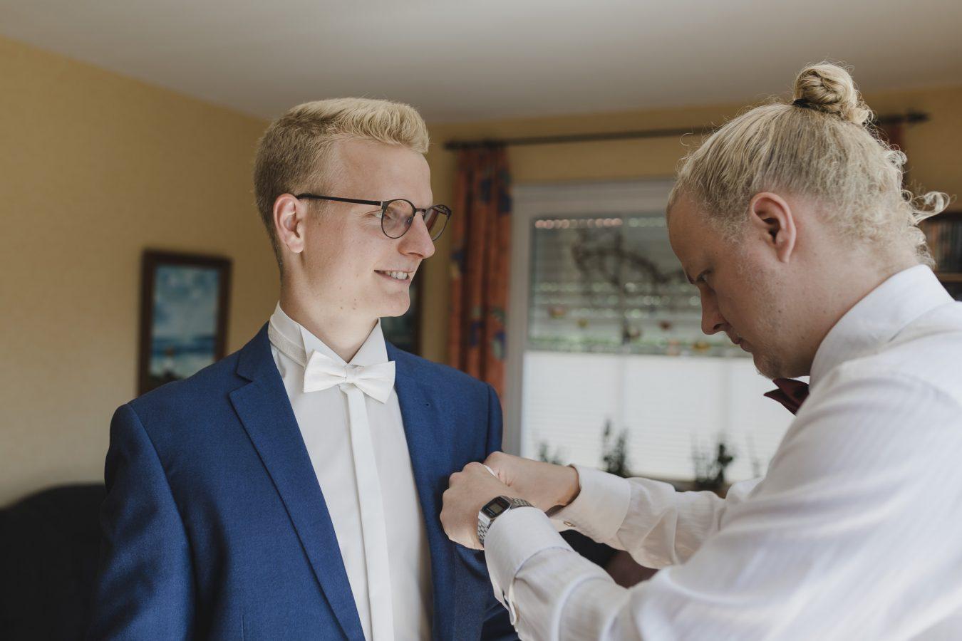 Getting Ready: der Trauzeuge steckt dem Bräutigam das Einstecktuch ins Jacket