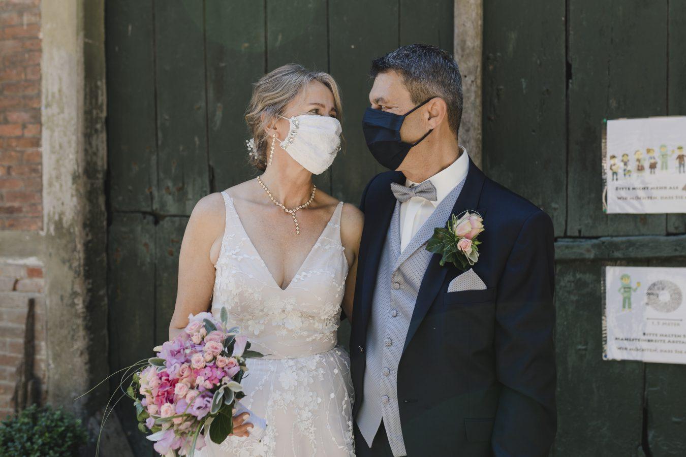 Das Brautpaar trägt eine Maske bei ihrer Corona-Hochzeit